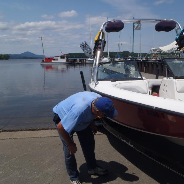 A man inspects his boat for aquatic invasive species