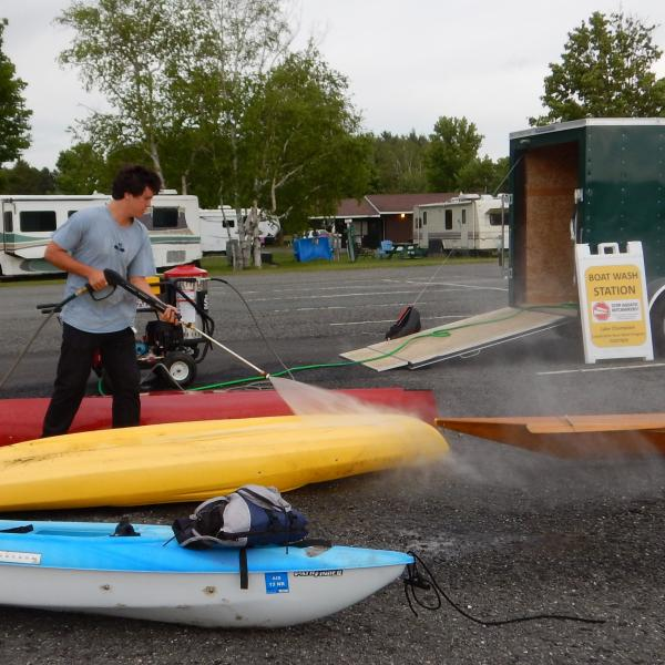 A public access greeter performs a watercraft decontamination.