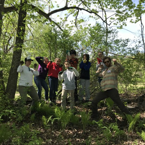 middle school students pose in front of the wooded area where they just removed invasive plants